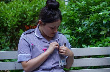 student nurse pinning badge to uniform