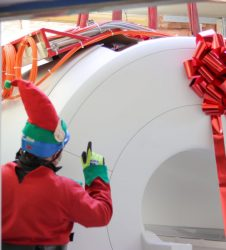crane operator dressed as elf guiding MRI scanner with red bow on through wall