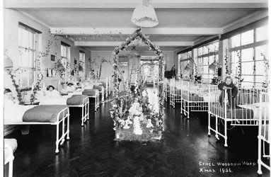 Children in beds and cots with ward centrepiece of flowers and dolls
