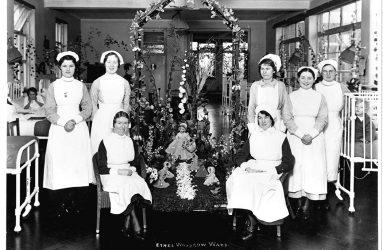 Nurses gathered round ward centrepiece of dolls and flowers