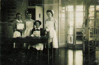 Nurses standing behind desk on ward