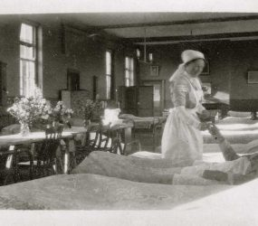 Nurse handing drink or medication to soldier on ward, flowers on central table