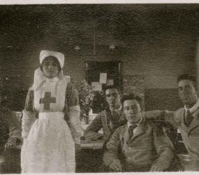 Nurse standing with seated soldiers wearing shirt, tie and jackets