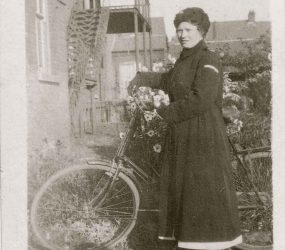 Cook in dark uniform posing with her bike in hospital grounds