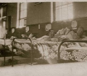 Soldiers sitting up in bed, floral and leaf patterned covers on the bed