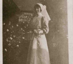 Nurse poses in garden, flowers and church in background