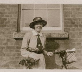 Nurse poses with her bike outside the hospital building