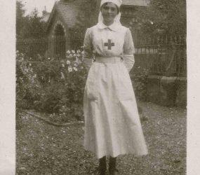 Nurse stands in the garden, church in the background