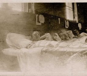 Three soldiers in bed pose for the camera