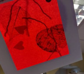 holding the artwork up to the light revealing the shadow cut out shapes within the tissue paper