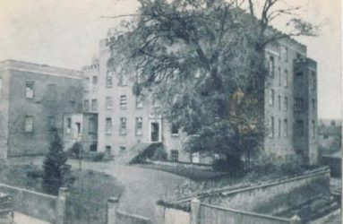 Photo of Infirmary building with large tree in foreground