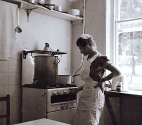 Woman in apron turning knob on gas stove to heat pots