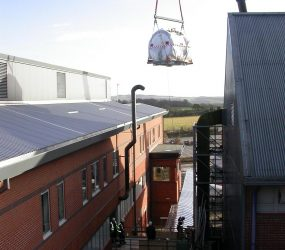 MRI scanner on the end of crane hook about to be lowered down towards the building
