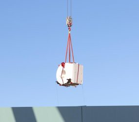 large white scanner suspended on the end of crane hook