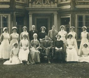 nurses and staff pose outside pillared entrance to Finch House