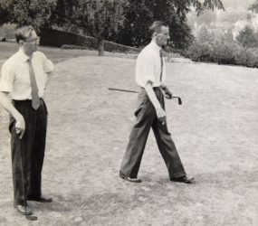Two men with golf clubs on the grass