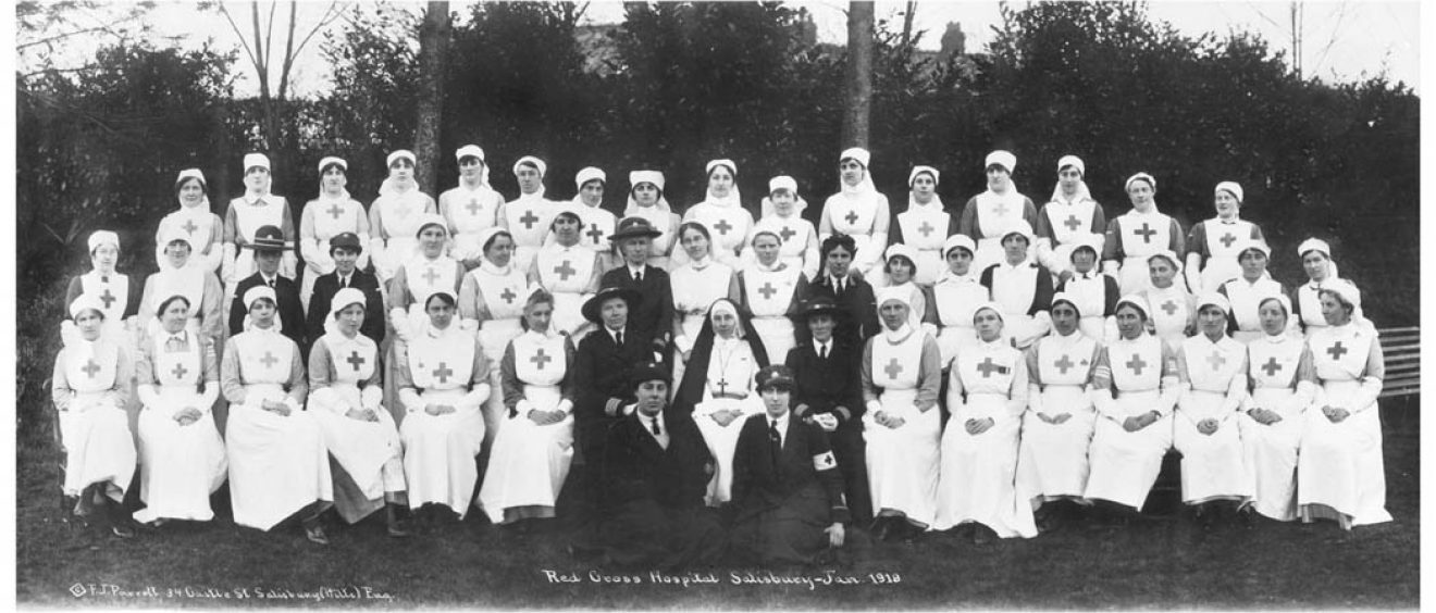 Nurses and other hospital staff seated and standing in rows for photograph