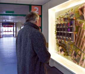 Man looking at model displayed on corridor wall