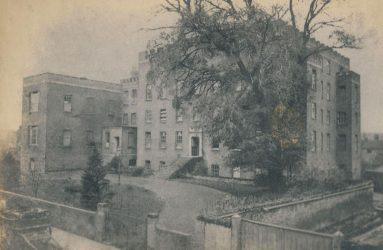 Infirmary viewed from the front, large tree in foreground