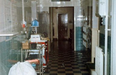 Trolleys, laundry bag and black and white tiled floor in corridor