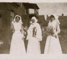 Nurses and nun in uniforms posing in garden outside hospital
