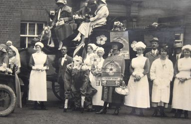 Ladies and gentlemen sitting in cart, with horses, nurses surrounding