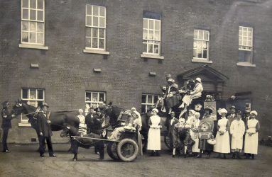 Ladies and gentlemen sitting in cart, with horses, with nurses standing in front of Infirmary