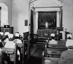 Banner hanging at front of chapel, nurses sit in pews