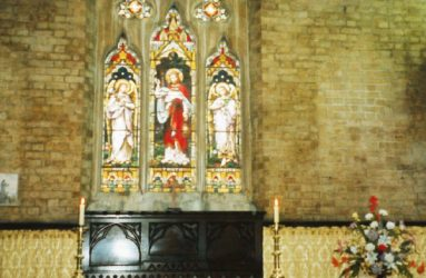 close up of altar showing panel shaped shadow areas either side of stained glass window
