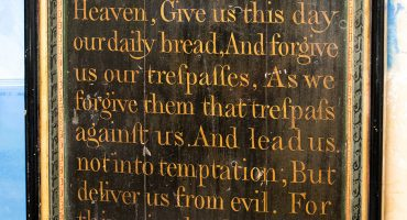 Oak panel arch shape with hand written lettering of Lord's prayer