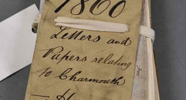 Bundle of old folded papers tied with cord and handwritten label saying 1860