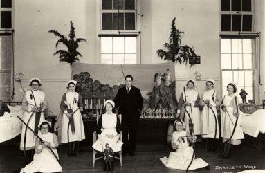 Nurses on ward holding bow and arrows