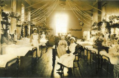 Nurses and patients in beds with garlands across the ward