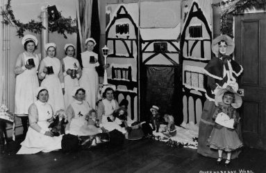 Nurses holding tankards with cardboard, snow covered Tudor house decoration