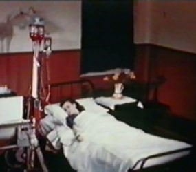 Female patient in bed with dialysis machine attached to arm