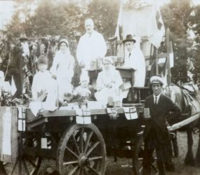 People dressed up on cart pulled by horse