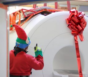man dressed as elf oversees delivery of MRI scanner wrapped with giant red bow