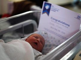 newborn baby in cot with certificate