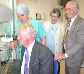 man looks through powerful microscope with staff member looking on