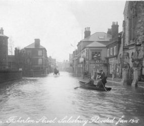 Three men in a rowing boat in flood water, horse and cart in the distance