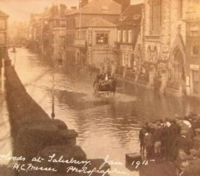 View of flooded street in front of the Infirmary building, horse and cart moving through the flood water