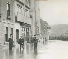 Soldier, two men and a boy in flat caps stand in flood water, larger crowd of people in distance by the clock tower
