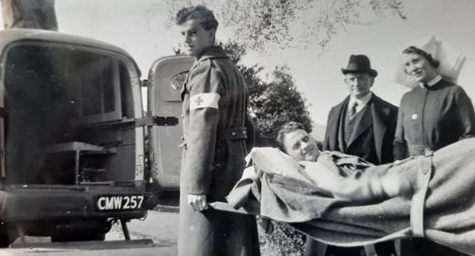 Gordon Richards being carried on stretcher towards back of ambulance