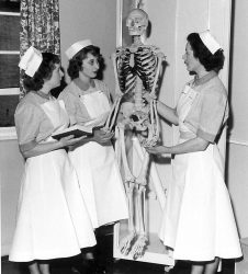 Three nurses studying a skeleton