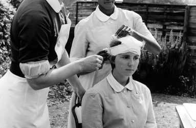 Two nurses bandaging another's head