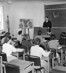 Nurses sat in rows at tables in front of blackboard