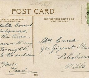 Message and address handwritten on back of postcard with half penny stamp and postmark