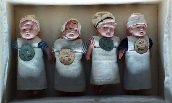 Small dolls in box dressed in scrap materials from nursing uniforms