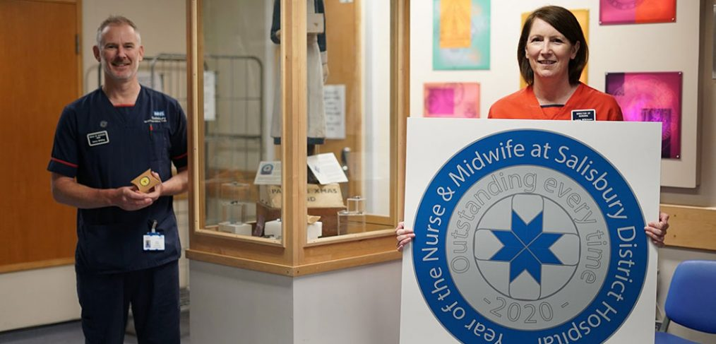 Lorna holding large badge design print out, standing next to display cabinet with Henry