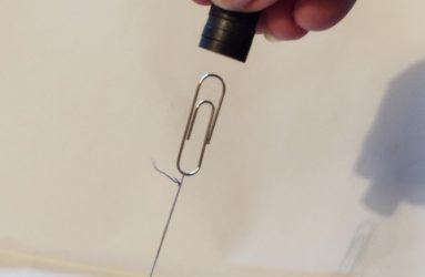 paper clip tied down with cotton thread attracted to the magnets held just above